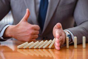 Sinnbildliche Aufnahme für erfolgreiches Krisen PR. Eine Person hält fallende Dominosteine auf und zeigt einen Daumen nach oben