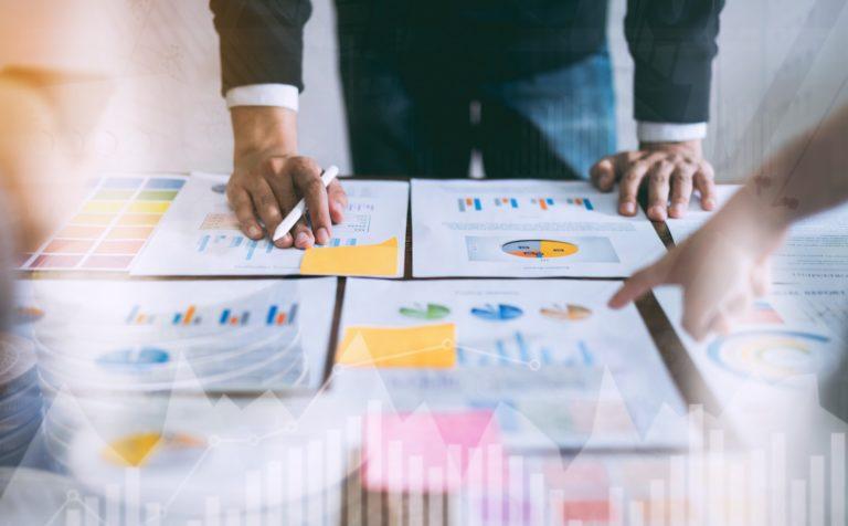 Remarketing Strategie Planung. Ein Tisch voller Zettel mit Grafiken und Statistiken.