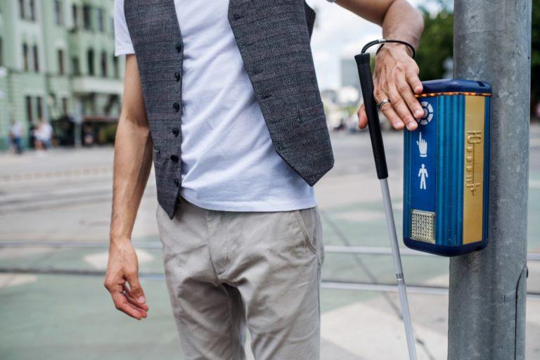 Eine blinde Person meistert die Herausforderungen des Alltags im Straßenverkehr