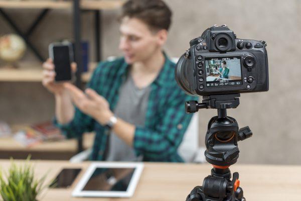 Ein Influencer präsentiert ein Produkt vor einer Kamera. Content Marketing Video Marketing