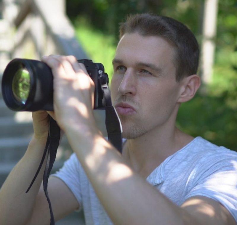 Sebastian Proprenter, Inhaber von nextlevelmedia.at. Beim Fotoshooting mit Kamera in der Hand.