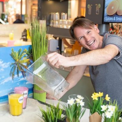 Pep Juice Villach Besitzer beim einschenken eines frischgepressten Saftes für während des Imagevideo Drehs